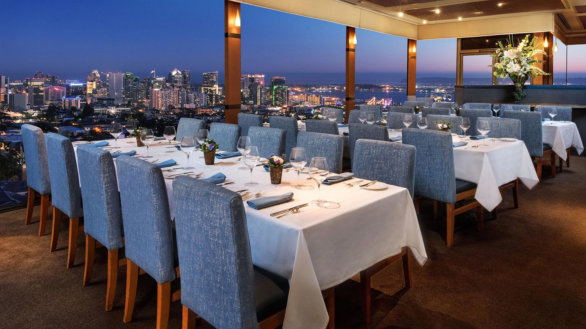 Group dining with view of San Diego at dusk